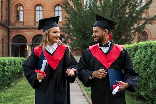 Portrait de deux diplômés multinationaux s'exprimant sur le campus universitaire en robes de graduation.