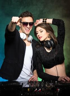 Portrait de deux dj avec mixer dans le club.