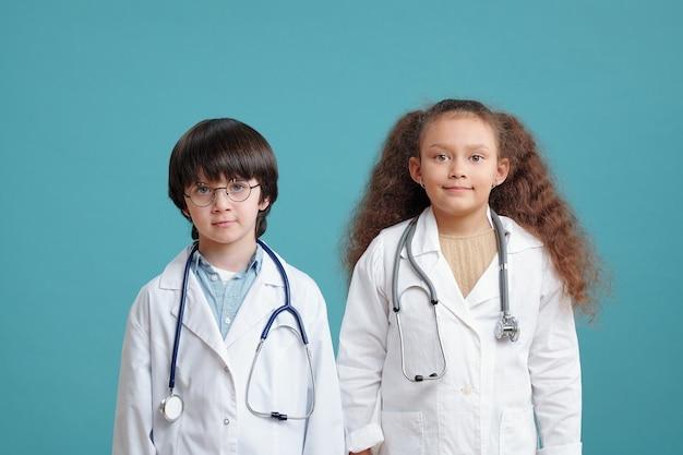 Portrait de deux enfants en blouse médicale souriant à la caméra sur le fond bleu