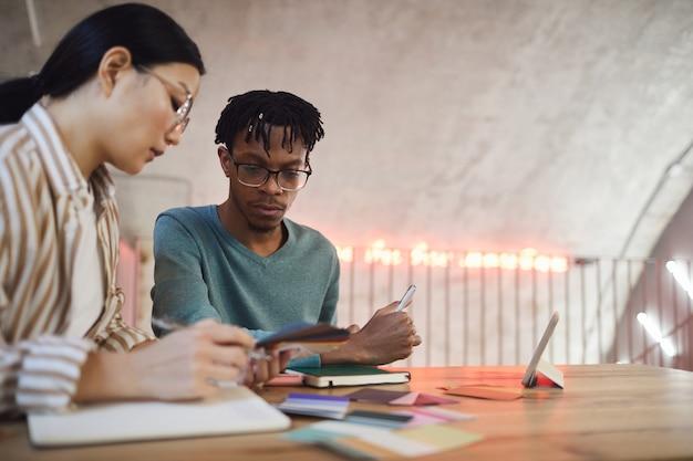 Portrait de deux étudiants contemporains travaillant ensemble sur un projet assis à table dans la bibliothèque