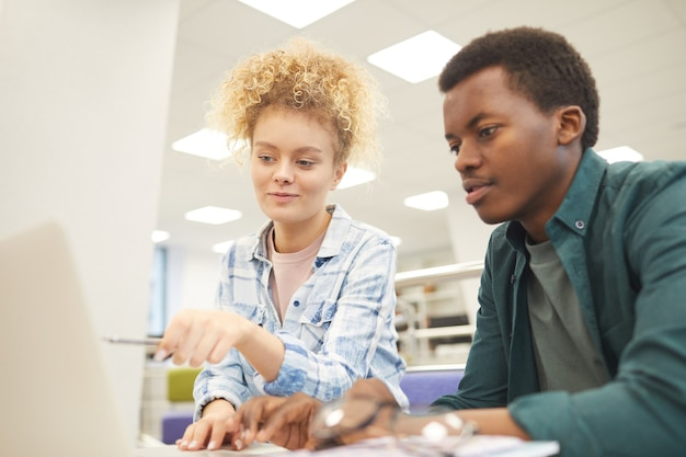 Portrait de deux étudiants, fille de race blanche et garçon africain, pointant sur l'écran du portable tout en travaillant