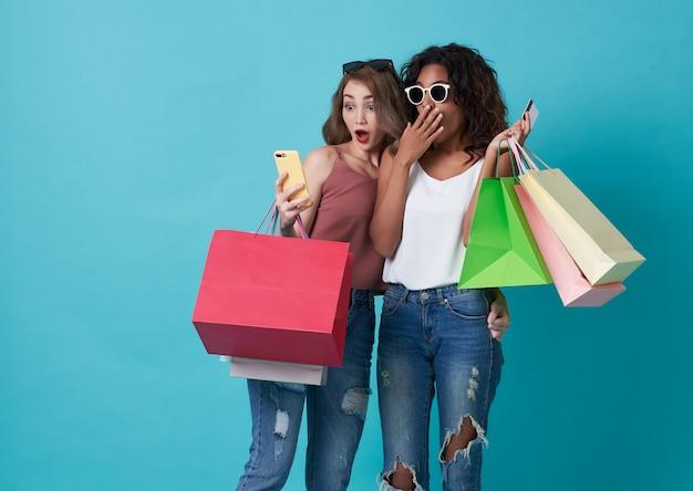 Portrait de deux excités jeune femme main tenant un téléphone mobile et un sac à provisions isolé sur fond bleu.