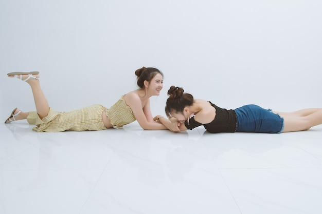 Portrait de deux femme heureuse en studio; émotions, personnes, adolescents et concept d'amitié sur fond blanc. deux femmes asiatiques rient drôles.