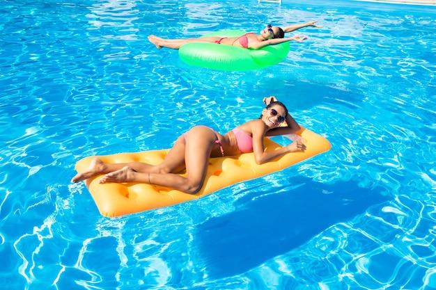 Portrait de deux femmes allongées sur un matelas pneumatique dans la piscine