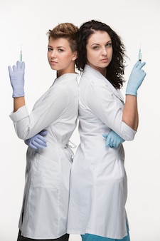 Portrait de deux femmes chirurgiens montrant des seringues