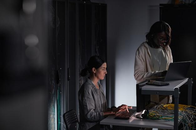 Portrait de deux femmes ingénieurs en informatique travaillant avec un ordinateur dans une salle des serveurs sombre, espace de copie