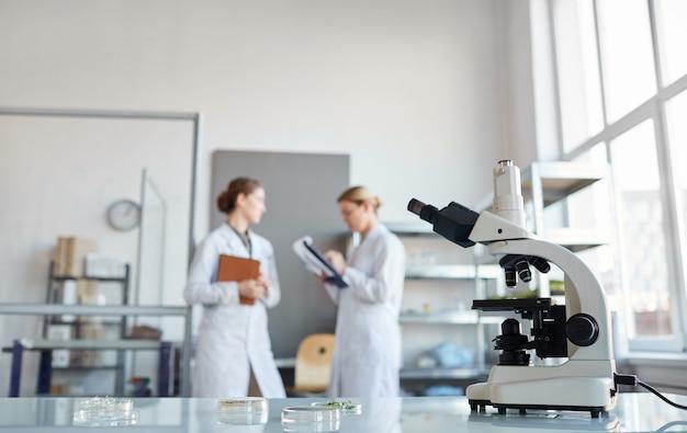 Portrait de deux femmes scientifiques discutant de la recherche en se tenant debout dans un laboratoire médical, se concentrer sur le microscope en premier plan, copiez l'espace