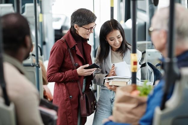 Portrait de deux femmes souriantes discutant dans un bus lors d'un voyage en transports en commun en ville, espace pour copie