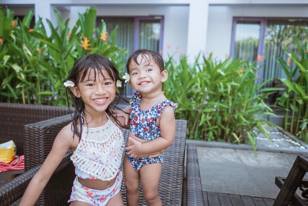 Portrait de deux fille asiatique en maillot de bain souriant regardant la caméra