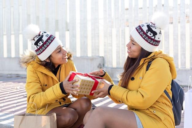 Portrait de deux filles assises sur le trottoir partageant des cadeaux. espace pour le texte.
