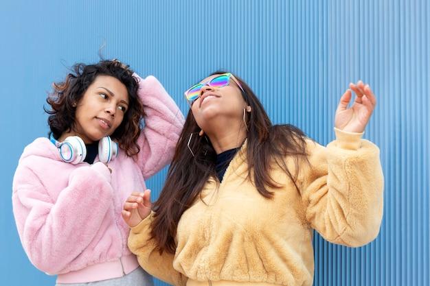 Portrait de deux filles brunes en vêtements informels sur fond bleu. l'un d'eux porte des lunettes de soleil aux couleurs du drapeau lgbt tandis que l'autre les regarde. espace pour le texte.