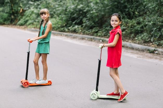Portrait, deux, filles, debout, pousser, scooter, rue