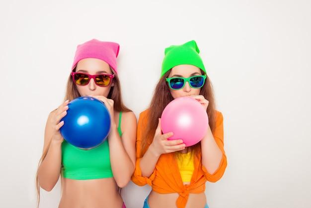 Portrait de deux filles hipster dans des verres soufflant des ballons