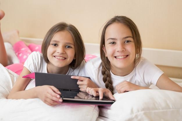 Portrait de deux filles souriantes au lit et à l'aide de tablette numérique
