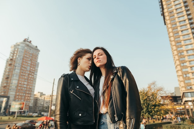Portrait deux filles en vêtements de rue debout sur l'herbe sur le paysage urbain