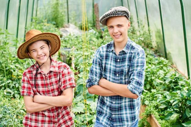 Portrait de deux frères dans une serre avec des plantes
