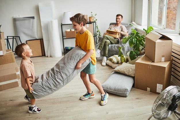 Portrait de deux garçons construisant un fort d'oreillers dans une chambre avec des boîtes pendant que la famille emménage dans une nouvelle maison.