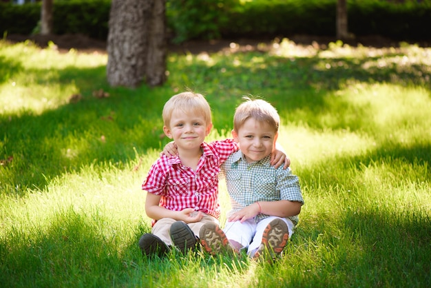 Portrait de deux garçons embrassant et riant fort à l'extérieur