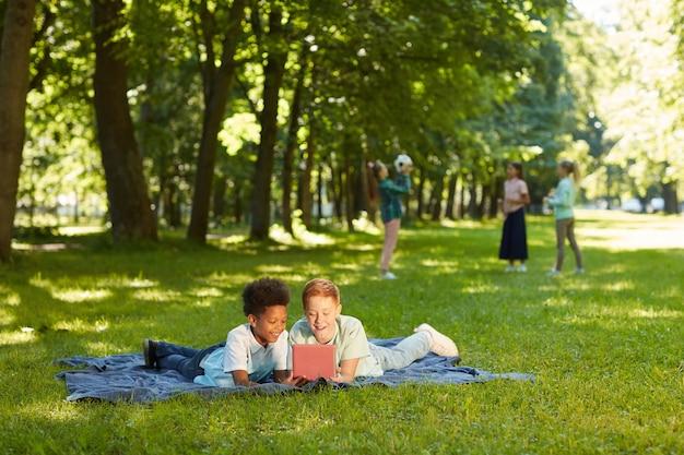 Portrait de deux garçons joyeux à l'aide de tablette numérique en position couchée sur l'herbe verte dans le parc à l'extérieur éclairé par la lumière du soleil