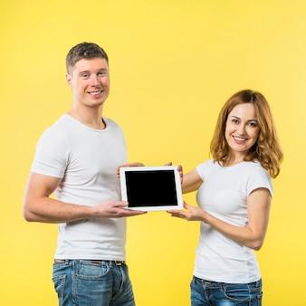 Portrait de deux heureux jeune couple montrant une tablette numérique écran noir sur fond jaune