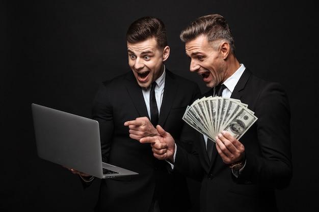 Portrait de deux hommes d'affaires excités vêtus d'un costume formel tenant un ordinateur portable et des billets d'argent isolés sur un mur noir