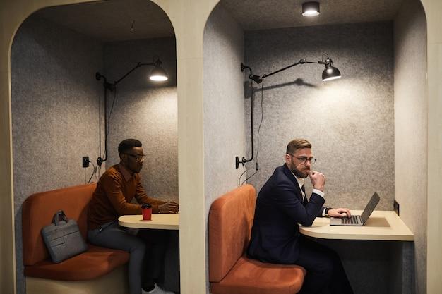 Portrait de deux hommes d'affaires modernes travaillant dans des cabines séparées au bureau ouvert, espace copie