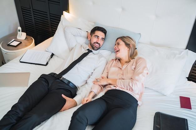 Portrait de deux hommes d'affaires prenant une pause du travail et allongé sur le lit à la chambre d'hôtel.