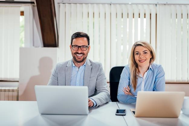 Portrait de deux hommes d'affaires prospères au bureau de coworking. regardant la caméra.