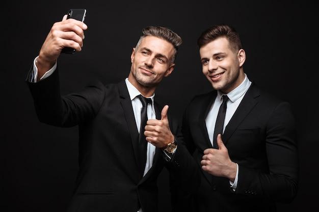 Portrait de deux hommes d'affaires satisfaits vêtus d'un costume formel prenant une photo de selfie sur un téléphone portable isolé sur un mur noir