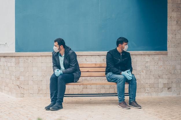 Portrait de deux hommes à la cour assis sur un banc inquiétant pendant la journée.