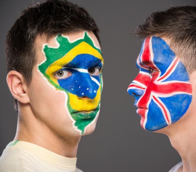 Portrait de deux hommes avec des drapeaux peints sur leurs visages.