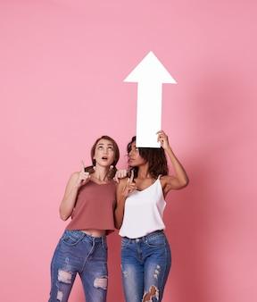 Portrait de deux jeune femme choquée debout avec sa flèche pointant vers l'espace de copie isolé sur rose.
