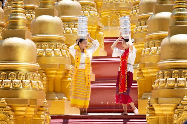 Portrait de deux jeune femme du myanmar dans un geste d'accueil traditionnel avec la pagode shwedagon