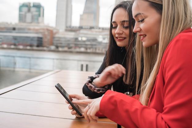 Portrait de deux jeunes amis à l'aide de leur téléphone portable assis au café. concept de mode de vie et d'amitié.