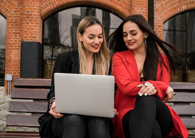 Portrait de deux jeunes amis à l'aide d'un ordinateur portable assis à l'extérieur. concept d'amitié et de style de vie.