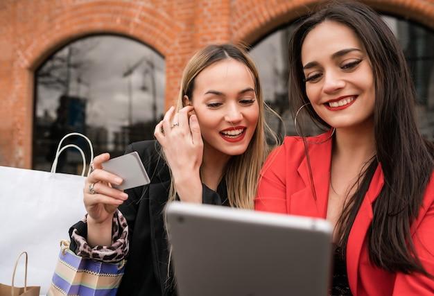 Portrait de deux jeunes amis, faire du shopping en ligne avec carte de crédit et tablette numérique assis à l'extérieur. concept d'amitié et de style de vie.