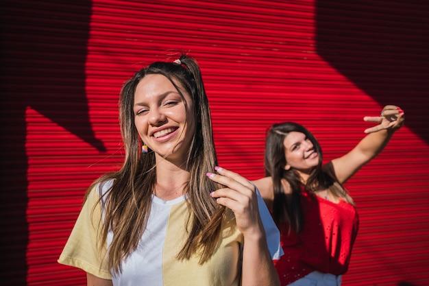 Portrait de deux jeunes amis heureux debout au sommet d'une porte rouge.