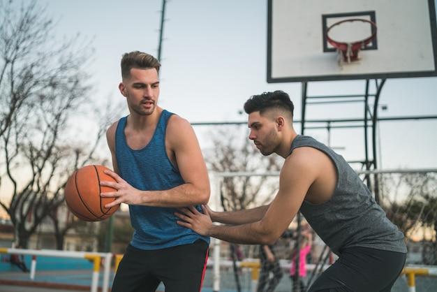Portrait de deux jeunes amis jouant au basket et s'amusant sur le terrain à l'extérieur. concept sportif.