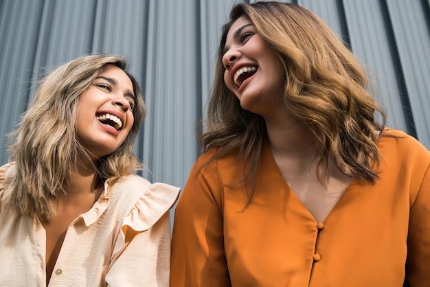 Portrait de deux jeunes amis, passer du bon temps ensemble et s'amuser en se tenant debout à l'extérieur.