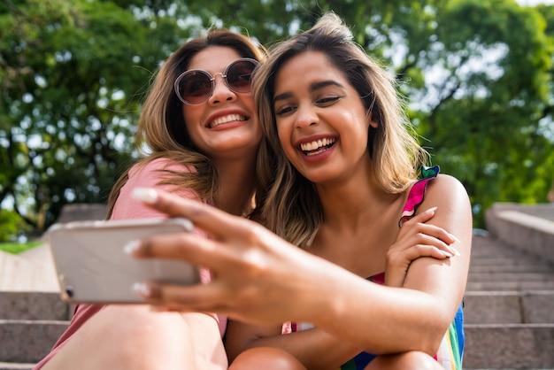 Portrait de deux jeunes amis souriants et prenant un selfie avec leur téléphone portable assis à l'extérieur. notion urbaine.