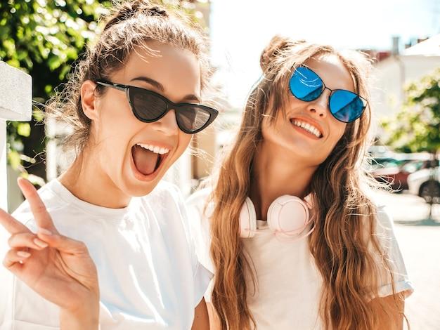 Portrait de deux jeunes belles femmes hipster souriantes dans des vêtements de t-shirt blanc d'été à la mode