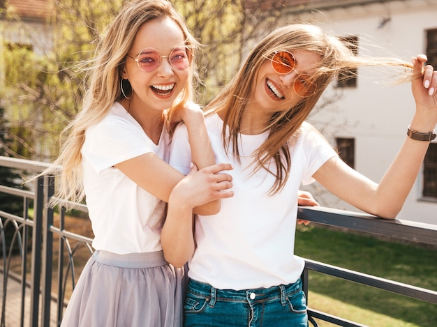 Portrait de deux jeunes belles filles blondes souriantes hipster dans des vêtements de t-shirt blanc à la mode d'été. . modèles positifs s'amusant avec des lunettes de soleil.