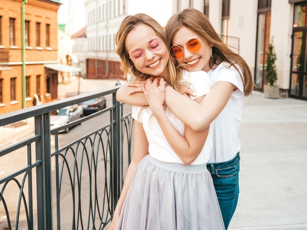 Portrait de deux jeunes belles filles blondes souriantes hipster dans des vêtements de t-shirt blanc à la mode d'été. . modèles positifs s'amusant.
