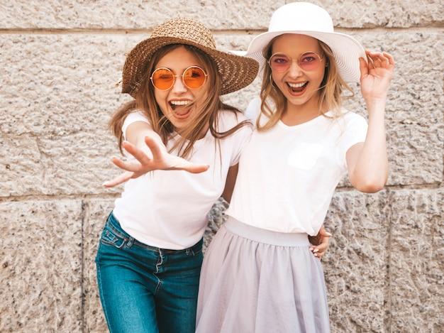 Portrait de deux jeunes belles filles blondes souriantes hipster dans des vêtements de t-shirt blanc à la mode d'été.