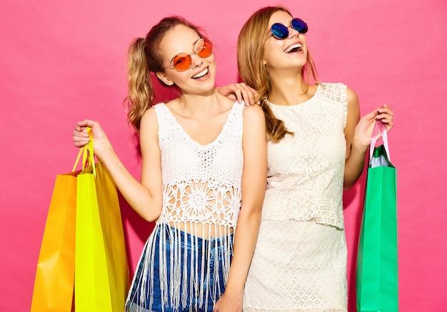 Portrait de deux jeunes femmes blondes souriantes élégantes tenant des sacs à provisions. femmes vêtues de vêtements d'été hipster. modèles positifs posant sur fond noir rose