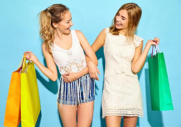 Portrait de deux jeunes femmes blondes souriantes élégantes tenant des sacs à provisions. femmes vêtues de vêtements d'été hipster. modèles positifs posant sur un mur bleu