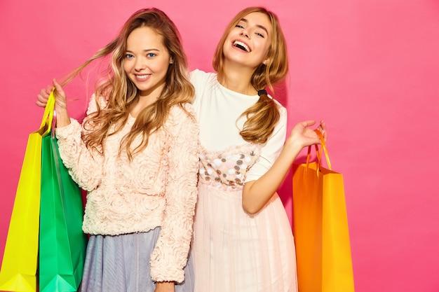 Portrait de deux jeunes femmes blondes souriantes élégantes tenant des sacs à provisions. femmes vêtues de vêtements d'été hipster. modèles positifs posant sur un mur rose