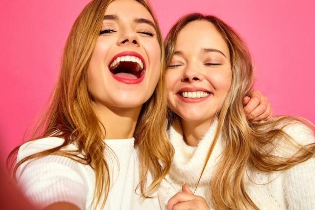 Portrait de deux jeunes femmes blondes souriantes élégantes