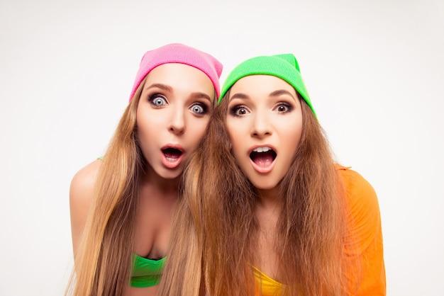 Portrait de deux jeunes femmes choquées avec la bouche ouverte
