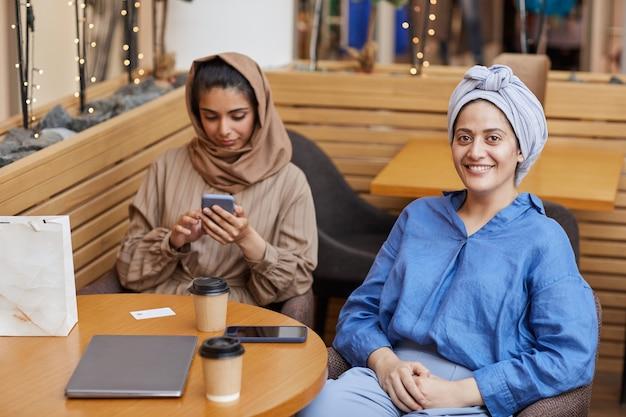 Portrait de deux jeunes femmes du moyen-orient se détendre dans un café tout en profitant du shopping dans le centre commercial, copy space